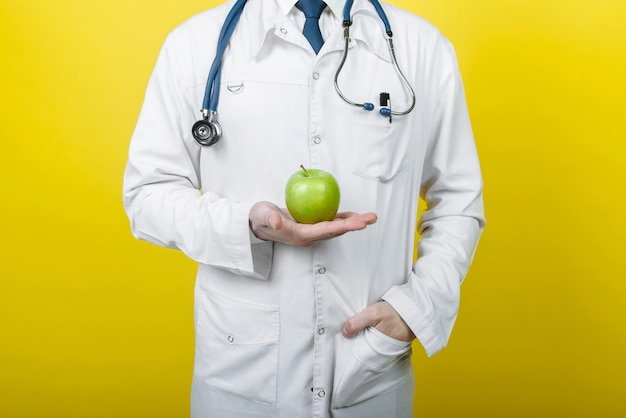 Man doctor nutritionist holds an apple in his hand. the concept of diet comparison. free place. proper nutrition