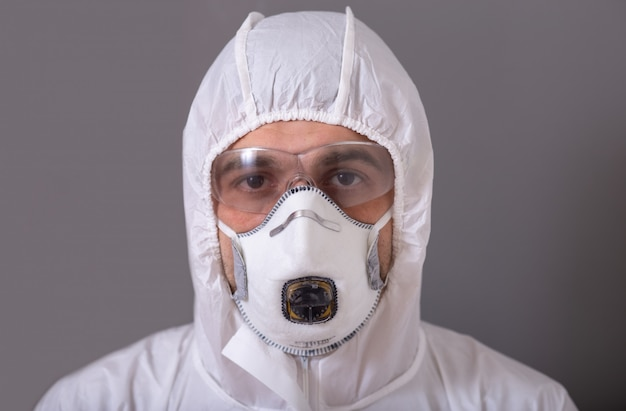 Man, doctor in protective suit, mask, glasses and gloves against bacterial and viral infection, covid 19, during the pandemic, tired, exhausted, stop, stay at home.