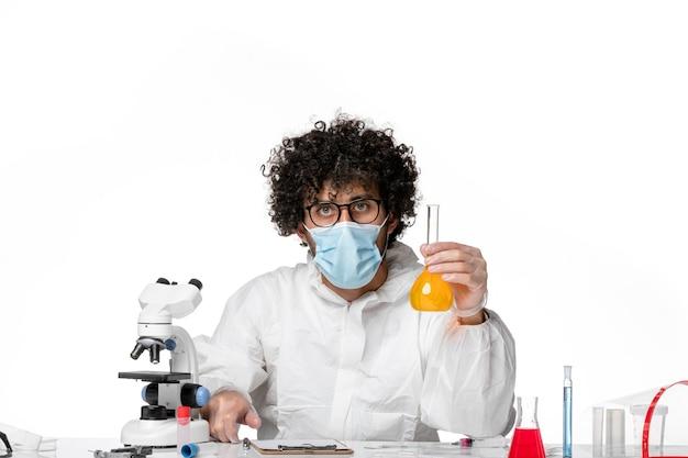 Uomo medico in tuta protettiva e maschera che tiene il pallone con soluzione gialla su bianco