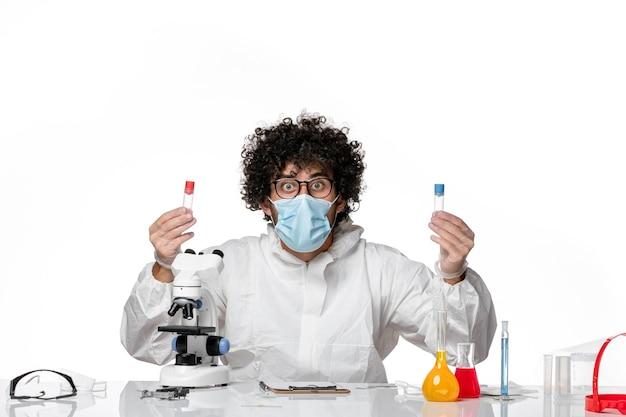 Uomo medico in tuta protettiva e maschera che tiene le boccette su bianco