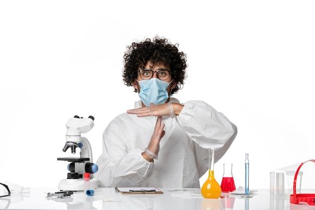 Uomo medico in tuta protettiva e maschera che mostra il segno t su bianco