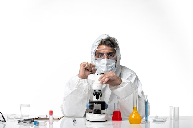 Man doctor in protective suit and mask sitting on light white