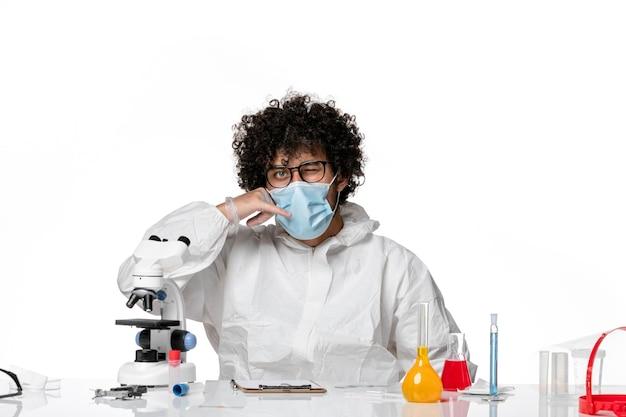 Uomo medico in tuta protettiva e maschera seduta su bianco