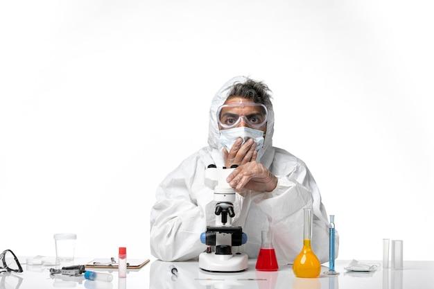 Medico uomo in tuta protettiva e maschera utilizzando il microscopio su bianco chiaro