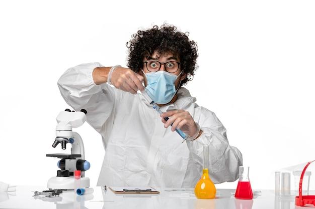 Uomo medico in tuta protettiva e maschera che lavora con soluzione e iniezione su bianco