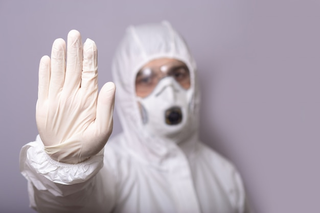 Man, doctor in protective suit, wearing mask, glasses and gloves against infection, covid 19, during pandemic, stops with his hand, stop, stay at home.