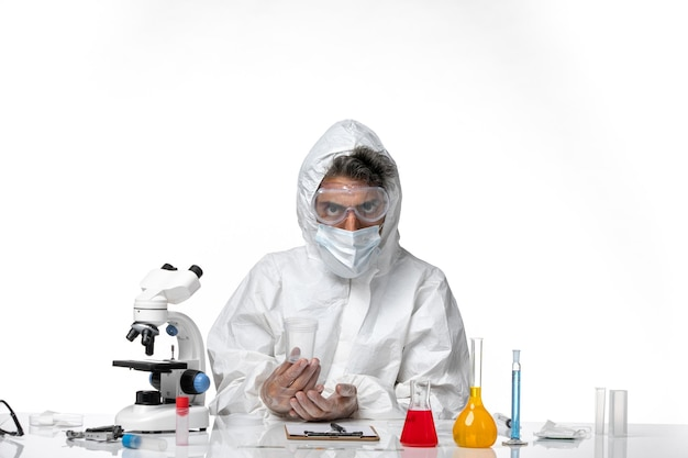 Man doctor in protective suit and with sterile mask holding empty flask on light white