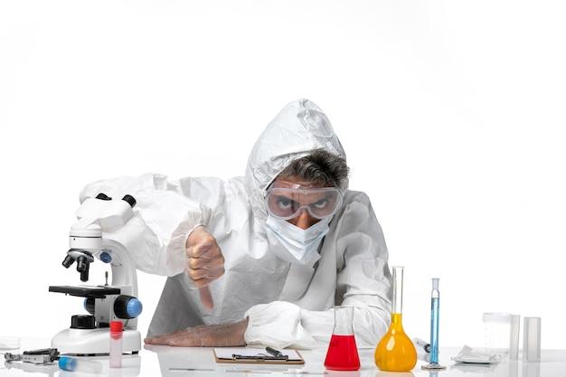 Medico uomo in tuta protettiva con maschera sterile su bianco chiaro