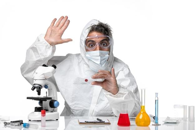 Medico uomo in tuta protettiva con maschera sterile che ondeggia su bianco chiaro