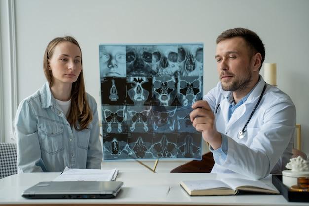 남자 의사는 xray 결과를 보여주고 그의 사무실에서 여성 환자에게 건강 문제를 설명합니다.