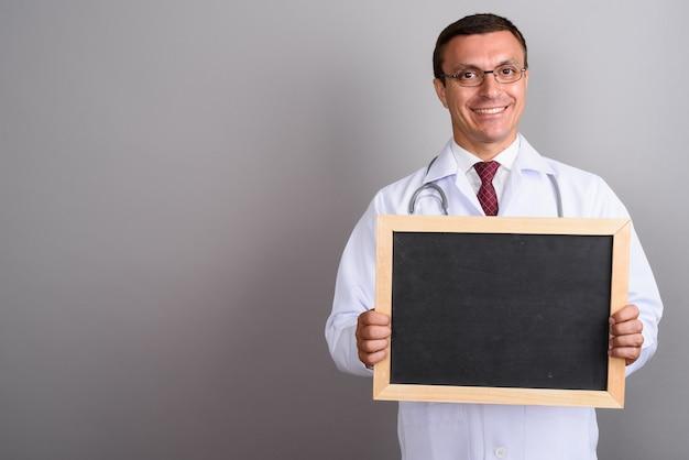 Укомплектуйте личным составом очки доктора нося против серой стены