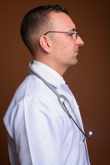 Man doctor wearing eyeglasses on brown