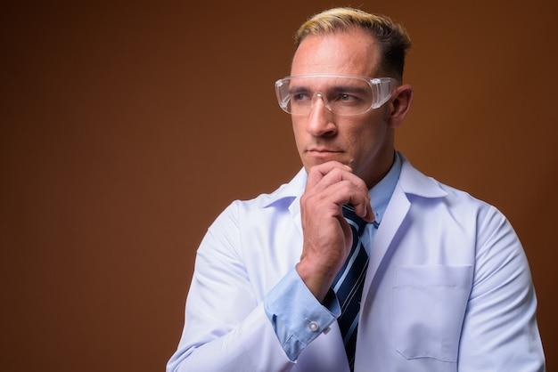 考えながら保護メガネをかけた男の医者