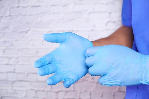 男性医師は医療用手袋を着用して、クローズアップ