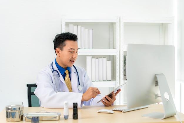 男性医師はラップトップで白衣とヘッドセットを話すビデオ会議を着ています。