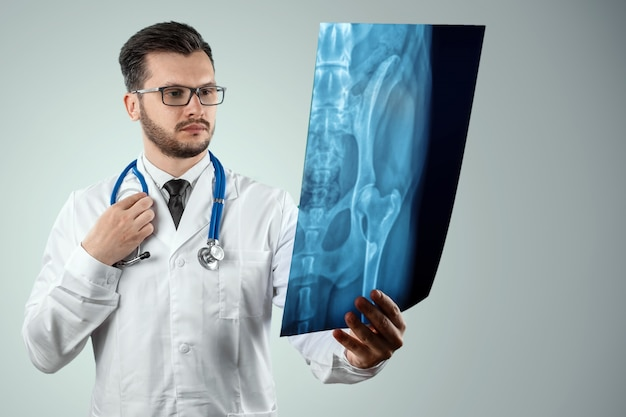 A man, a doctor in a white coat, carefully looking at the picture.