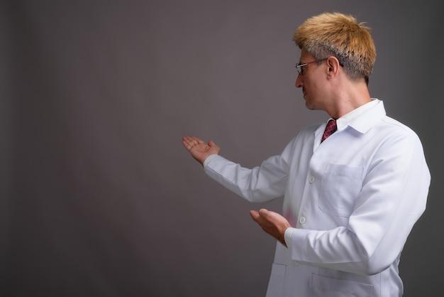 회색 벽에 금발 머리를 가진 남자 의사