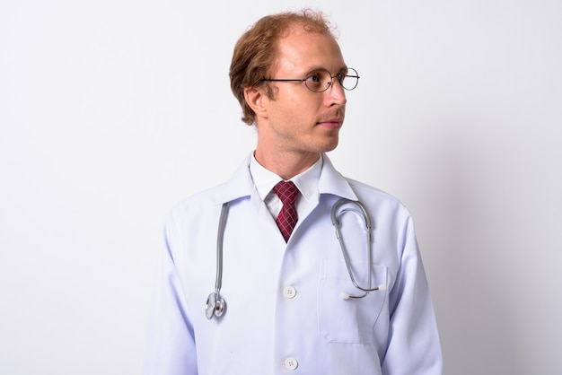 Man doctor with blond hair wearing eyeglasses against white wall