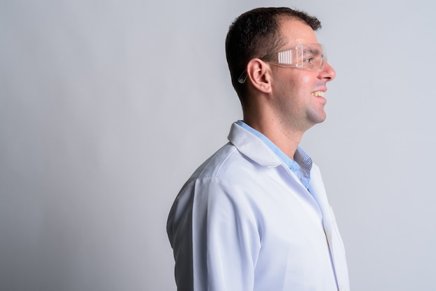 Man doctor with protective glasses on white