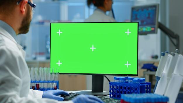 바이러스 진화를 분석하는 현대적인 시설을 갖춘 실험실에서 녹색 화면으로 pc에서 일하는 남자 의사. 크로마 키, 격리된 모형 디스플레이가 있는 장치에서 백신 연구를 하는 미생물학자 팀.