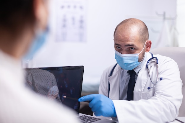 Man doctor and young patient with protection mask talking about virus evolution sitting on chair in front of laptop in hospital office clinic. medical worker showing the symptoms pointing on desktop