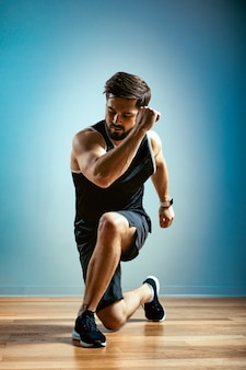 Человек делает функциональные упражнения в тренажерном зале на сером фоне