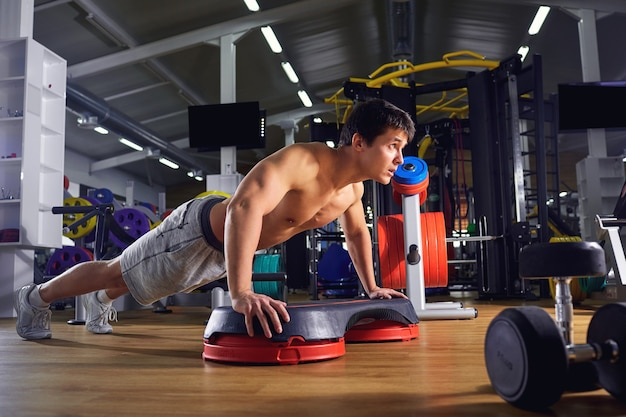 A man does pushups from floor in the gym