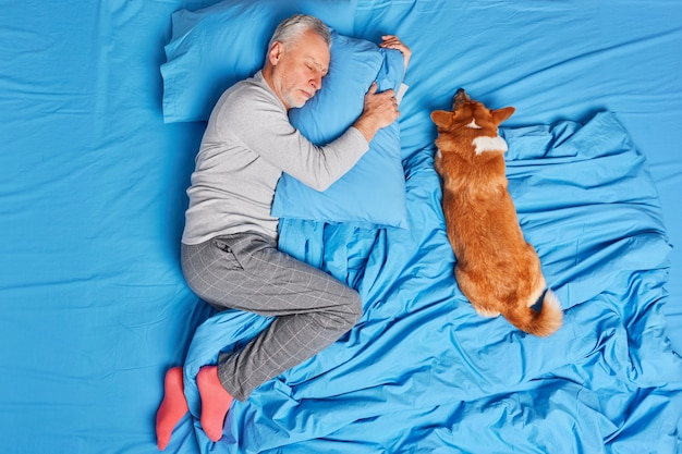 Man dog owner of old age sleeps peacefully together with pet poses in bed wears pajama and socks lying on soft pillow sees sweet dreams. mature bearded man rests at bedroom. people slumber concept