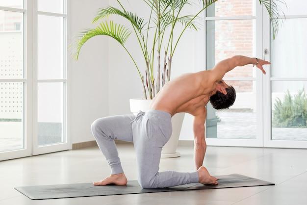 コピースペースを備えた健康とフィットネスのコンセプトで、コピースペースを備えたハイキージムで体と筋肉の可動性と柔軟性を高めるためにバックベンドとツイストヨガのポーズをとっている男性