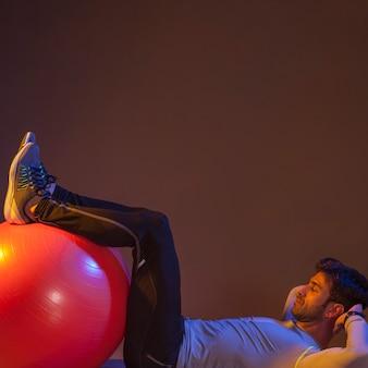 Man doing abdominal crunches near fitball