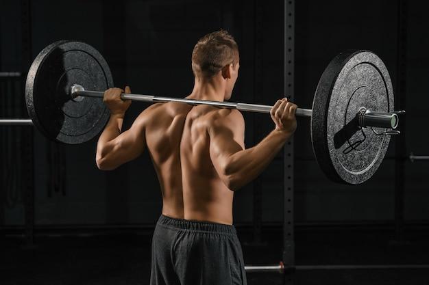 バーベルを使ってバックスクワット運動をしている男性。ジムでのクロスフィット トレーニング。