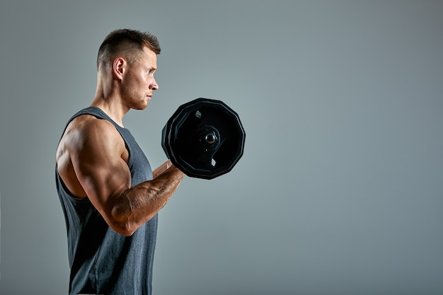 背中のトレーニングをしている人、灰色の背景の上のスタジオでバーベルの行。コピースペース、広告用スポーツバナー