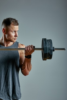 Man doing back workout, barbell row in studio over gray space. copy space