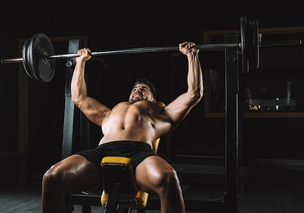 Man doing bench presses with weights in a bar indoors