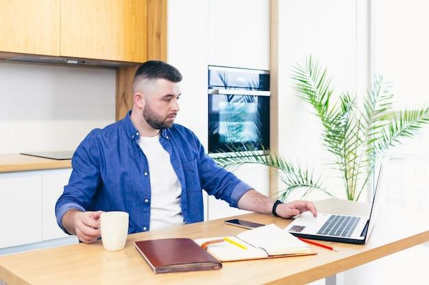 Человек занимается бизнесом, оставаясь дома, сидя на кухне за столом и используя ноутбук