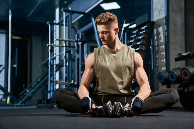 Man doing butterfly stretch on floor in gym.