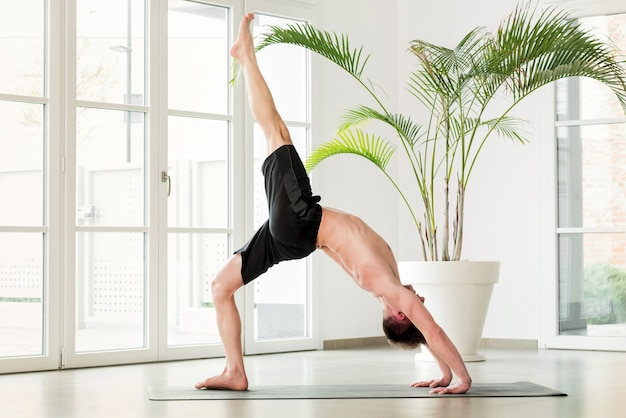 Man doing a chakrasana yoga pose or backbend stretch to increase mobility and flexibility of his body in a high key gym with copyspace in a health and fitness concept