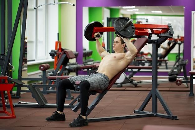 垂直ベンチプレス機で胸のエクササイズをしている男