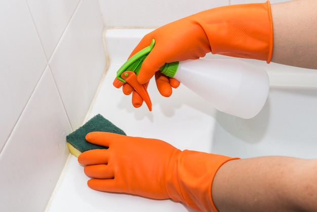 Man doing chores in bathroom at home, cleaning sink and faucet with spray detergent