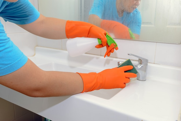 Man doing chores in bathroom at home, cleaning sink