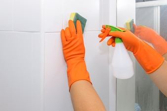 Man doing chores in bathroom at home, cleaning wall with spray detergent