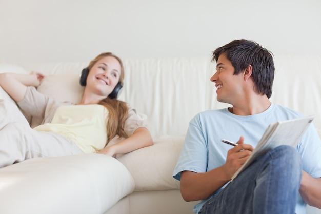 그의 여자 친구가 음악을 듣고있는 동안 남자는 낱말을하고