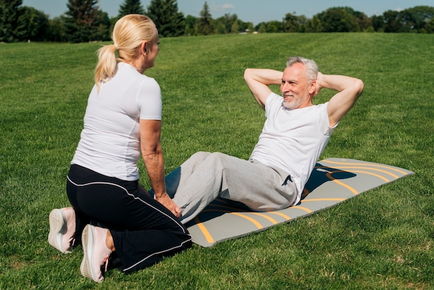 Man doing crunches and being held by woman