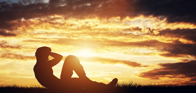 Man doing crunches outdoors in the sunset.