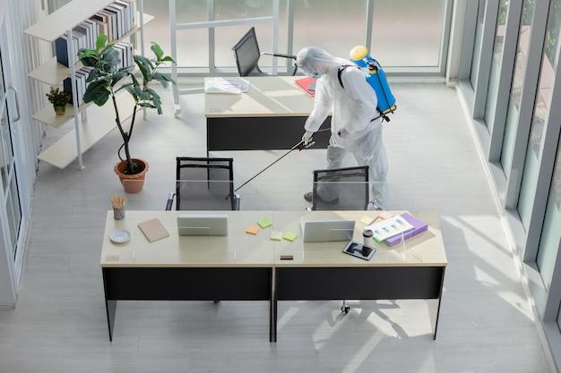 Человек делает дезинфекцию в офисе