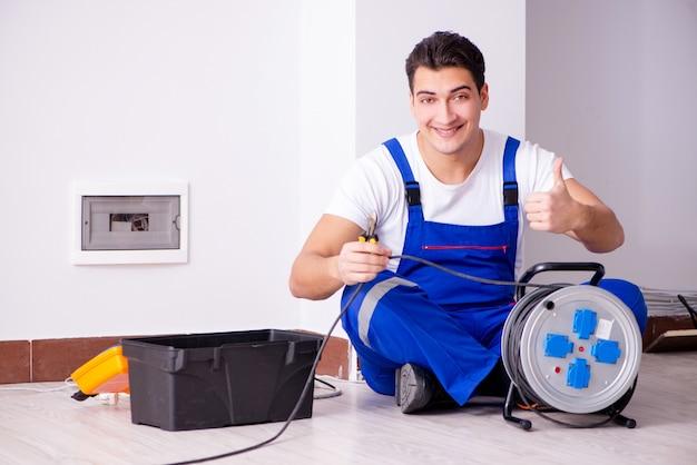 自宅で電気修理をしている男