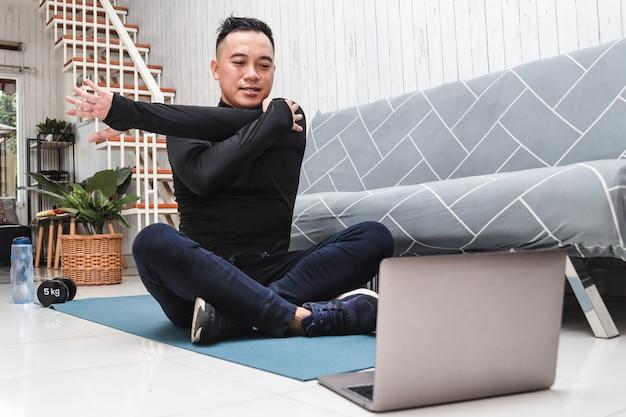 座ってオンラインでノートパソコンを見ながら腕を伸ばして自宅から運動をしている男