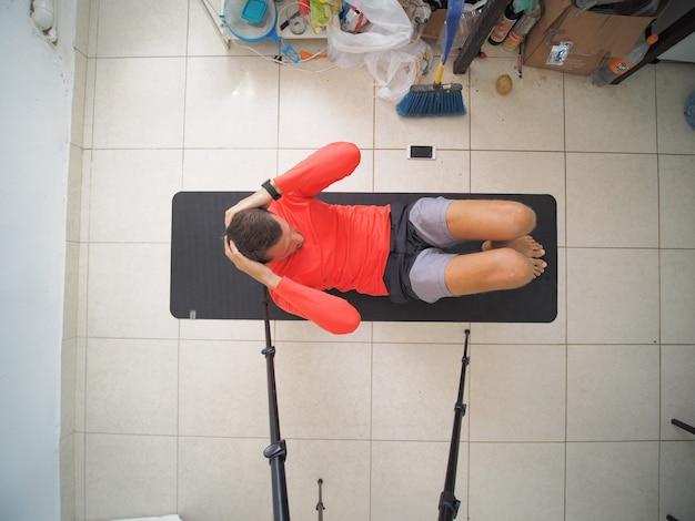 체육관 매트에 누워 복근 운동을 하는 남자. 평면도.
