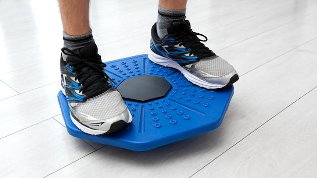 Человек делает упражнения на доске баланса