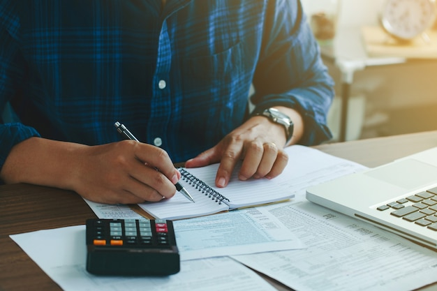 Man doing finances and calculate about cost to real estate investment and in other tax system